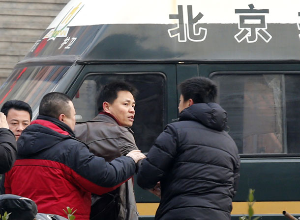 Zhang Xuezhong (Center), a lawyer for Chinese dissident Zhao Changqing, argues with plain-clothed policemen as he refuses to show them his identification card when he was stopped and questioned by them on his way to court to attend Zhao's trial in Beijing Jan. 23, 2014. (Photo: Reuters)