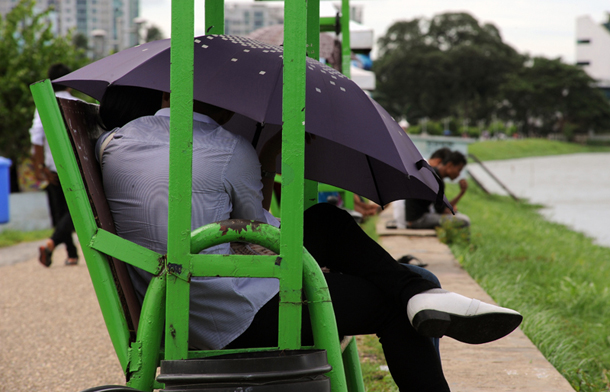 A young couple hides under an umbrella for extra privacy on the embankment of Inya Lake in Rangoon. (Photo: Steve Tickner / The Irrawaddy)