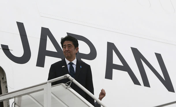 Japan's Prime Minister Shinzo Abe disembarks from an aircraft upon his arrival at the airport in New Delhi