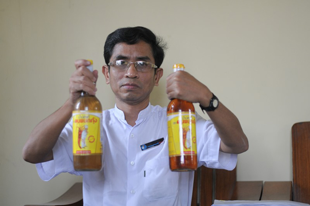 Ba Oak Khine, founder of the Consumer Protection Association, holds a bottle of fish sauce in his left hand which he says is fake, and another bottle in his right hand which he says is authentic. (Photo: Sai Zaw / The Irrawaddy)