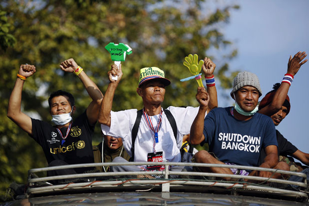 Thailand, politics, unrest, political violence, tourismAnti-government protesters travel atop a bus near the Interior Ministry building that is being surrounded by fellow protesters in Bangkok Feb. 5, 2014. (Photo: Reuters)