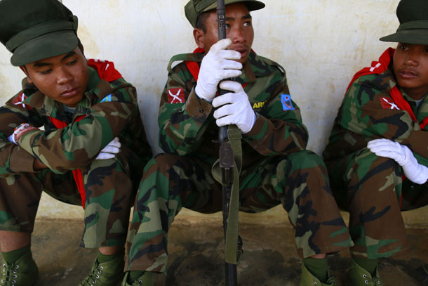 A Ta'ang National Liberation Army soldier holds a gun while sitting with fellow soldiers during the 51st anniversary of the Ta'ang National Resistance Day at Homain, Nansan Township, in northern Shan State on Jan. 12, 2014. (Photo: Reuters / Soe Zeya Tun)