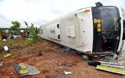 An overturned bus serves as a stark reminder of the dangers of travel on Myanmar's longest highway. (Photo: Aung Nay Myo / The Irrawaddy)