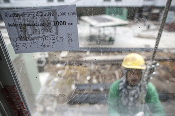 A multi-language sign, written the Thai, Cambodian and Burmese languages, is seen as a construction laborer works at a building site in Bangkok on June 18, 2014. (Photo: Reuters / Athit Perawongmetha)