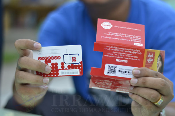 A mobile phone user in Mandalay holds up a newly bought Ooredoo SIM card. (Photo: Teza Hlaing / The Irrawaddy)