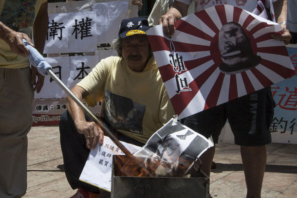 A protester burns a portrait of Japanese Prime Minister Shinzo Abe to rally against Abe's push to expand Japan's military role abroad, near the Japanese consulate in Hong Kong on July 4, 2014. (Photo: Reuters / Tyrone Siu)