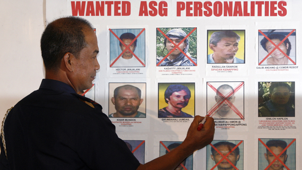 Philippine police chief Director General Jesus Verzosa studies a poster of Abu Sayyaf militants in Manila on Feb. 25, 2010. (Photo: Reuters / Erik de Castro)
