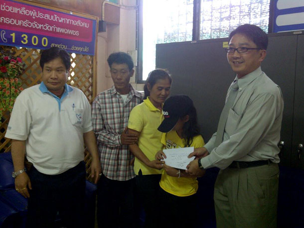 Burmese labor official Naing Htun hands 25,000 baht ($840) to a Karen girl who escaped from a Thai couple accused of inflicting severe abuse on her for five years. (Photo: President's Office Facebook page)
