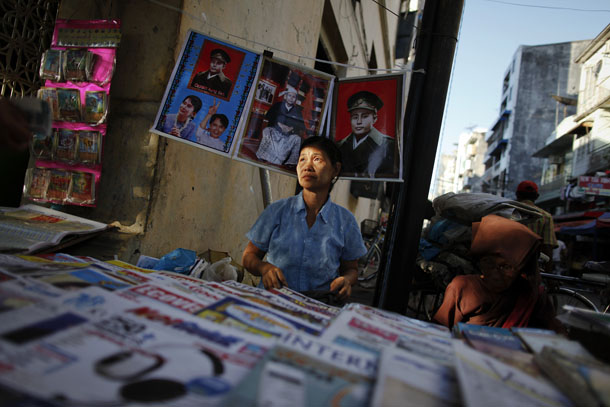 A newspaper vendor sits under pictures of pro-democracy leader Aung San Suu Kyi and her father, the country's independence hero General Aung San in central Rangoon. (Photo: Reuters)