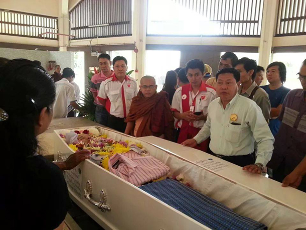 Myo Pai, a leader of a Kuala Lumpur-based free funeral services group, standing right in a white shirt, beside the coffin of Ko Tony on Wednesday, before he was killed. (Photo: Sakhunna Ung)