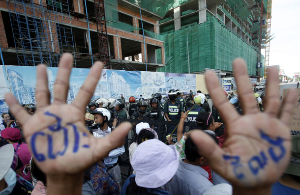 "A man, with his hands painted with words that translate to ""Release,"" demonstrates to demand the release of five opposition members of parliament, as police officers block a street near the Phnom Penh Municipal Court in central Phnom Penh on July 16, 2014. (Photo: Reuters)"
