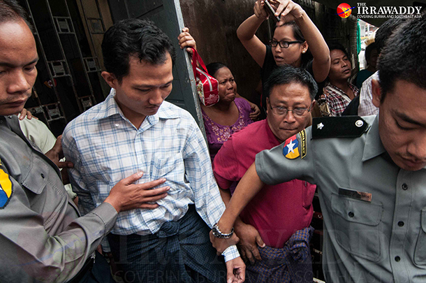 An editor of Bi Mon Te Nay journal is escorted out of the Pabedan Township Court in Rangoon on July 22. (Photo: Sai Zaw / The Irrawaddy)