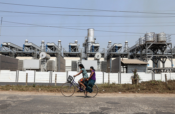 Women cycle past a gas power plant in Rangoon's Thaketa Township. (Photo: JPaing / The Irrawaddy)
