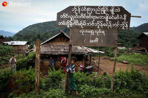 """A boy stands below a signpost that bears the TNLA's warning in the Palaung language: """"Opium and drug use and selling are strictly prohibited in the Ta'ang area."""" (Photo: JPaing / The Irrawaddy)"""