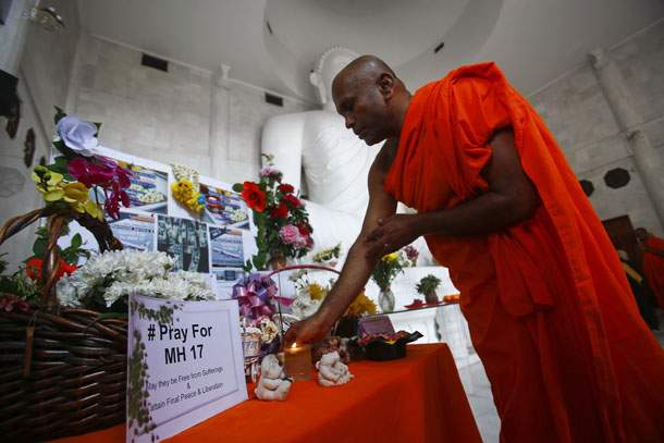 A monk performs a prayer during a special vigil for victims of the downed Malaysia Airlines Flight MH17, inside a Buddhist temple in Kuala Lumpur on July 20, 2014. (Photo: Reuters / Samsul Said)