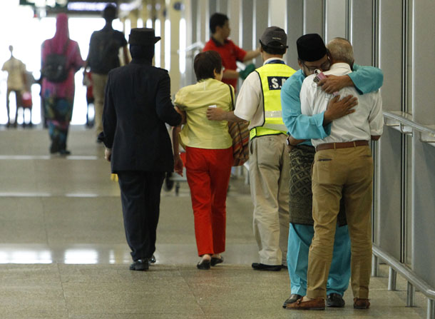 A man (in blue), whose family was onboard Malaysia Airlines MH17, consoles another man who had just arrived with his wife to receive confirmation that their daughter's family was onboard the plane, at Kuala Lumpur International Airport in Sepang July 18, 2014. (Photo: Reuters)