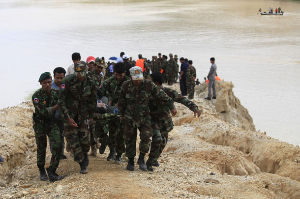 Cambodia's soldiers carry a body which rescue workers found at the site where a Cambodian military helicopter crashed on the outskirts of Phnom Penh on Monday. (Photo: Pring Samrang / Reuters)