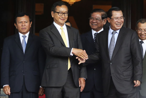 Cambodia's Prime Minister Hun Sen (2nd R) shakes hands with Sam Rainsy (2nd L), president of the CNRP after a meeting at the Senate in Phnom Penh on Tuesday. (Photo: Pring Samrang / Reuters)
