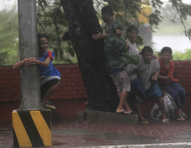 A boy hugs an electric post while other people take cover under a tree as strong winds brought by Typhoon Rammasun, locally called Glenda, battered the capital, metro Manila July 16, 2014. (Photo: Reuters)