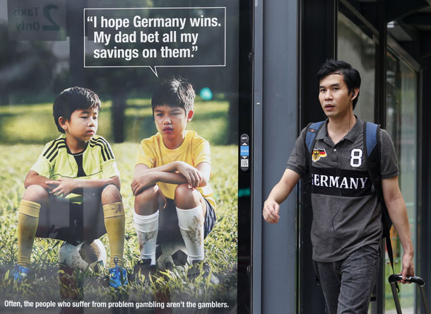 A man walks past a World Cup anti-gambling advertisement at a taxi stand in Singapore July 9, 2014. Singapore has scored an own goal with the World Cup anti-gambling ad. (Photo: Reuters)