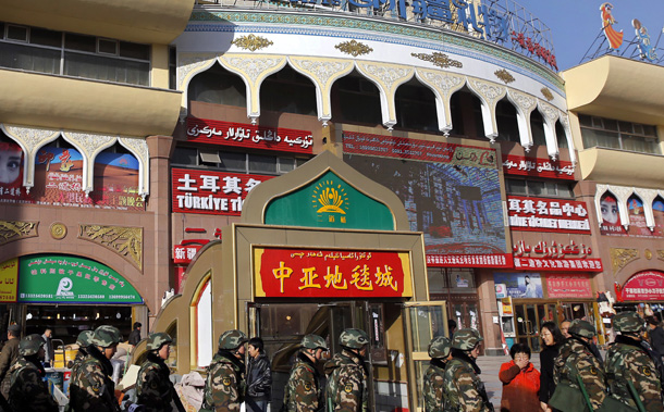 Paramilitary policemen walk past Erdaoqiao Grand Bazaar in Urumqi, Xinjiang Uighur autonomous region, November 17, 2013. (Photo: Reuters)