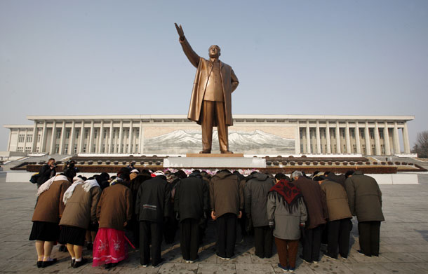 "A group of people bow at the base of the giant bronze statue of the state founder and late ""Great Leader"" Kim-Il Sung in the North Korean capital of Pyongyang on February 26, 2008. (Photo: Reuters)"