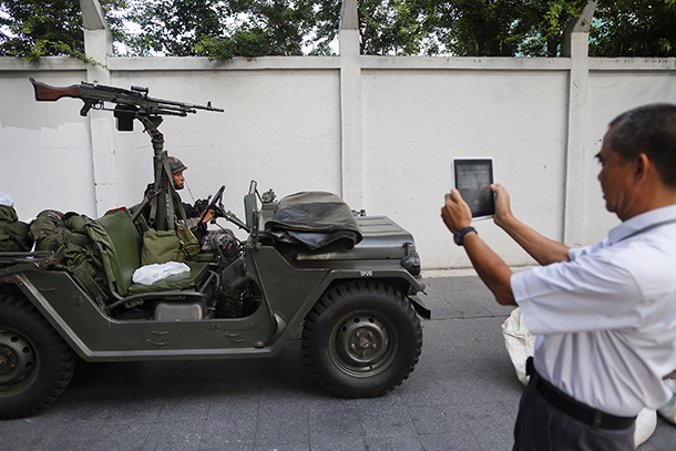 Thai soldiers take up a position on a main road in Bangkok on May 20, 2014, as a bystander takes a photo. (Photo: Reuters)