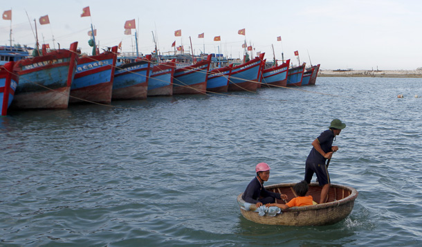 Fisherman Nguyen Hap, right, paddles a boat to transport Bui Van Minh and his son Bui Van Chau to Minh's damaged fishing boat at a quay of Ly Son port, in Vietnam's central Quang Ngai province on July 1, 2014. (Photo: Reuters / Kham)