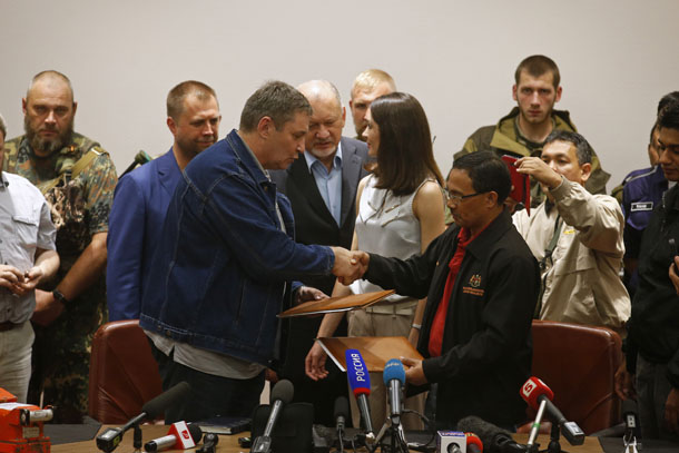 A representative, front left, from pro-Russian separatists shakes hands with Colonel Mohamed Sakri of the Malaysian National Security Council after handing over of Malaysia Airlines flight MH17's black boxes, in Donetsk on July 22, 2014. (Photo: Reuters / Maxim Zmeyev)