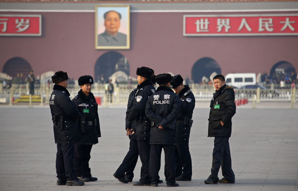 Police stand at Tiananmen Square in front of the portrait of China's late leader Mao Zedong. (Photo: Reuters)