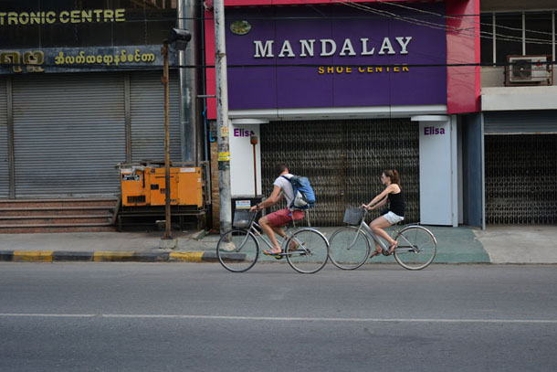 Two foreign tourists cycle down 26th (B) street on the afternoon of July 4. The normally busy street in central Mandalay was deserted because of inter-communal unrest that began on July 1. (Photo: The Irrawaddy)