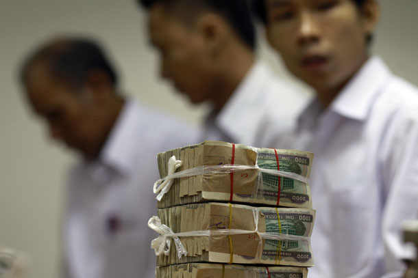 A stack of 1,000 kyat banknotes is seen, as employees count money at Yoma Bank in Rangoon. (Photo: Reuters)