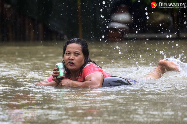 A woman drinks a Heineken beer while swimming through the floods on an inflated tire on Wednesday. Hundreds of residents of Pegu Town have been suffering from severe flooding in recent days following heavy downpours. (Photo: JPaing / The Irrawaddy)