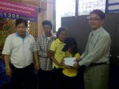 A Burmese labor official hands 25,000 baht ($840) to a Karen girl who escaped from a Thai couple accused of inflicting severe abuse on her for five years. (Photo: Facebook / President's Office)