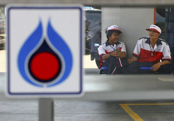Workers are seen awaiting customers behind a PTT logo at a fuel station in Bangkok. (Photo: Reuters)