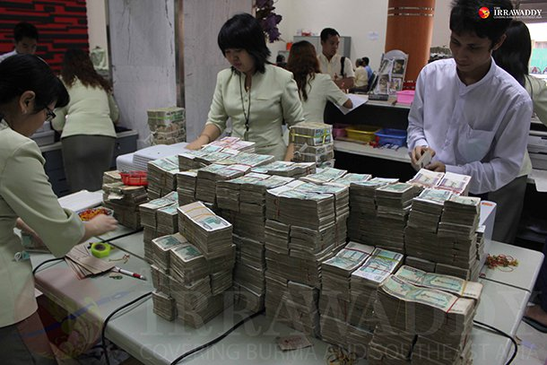 Bank staff in Rangoon count piles of Burmese kyat. (Photo: JPaing / The Irrawaddy)