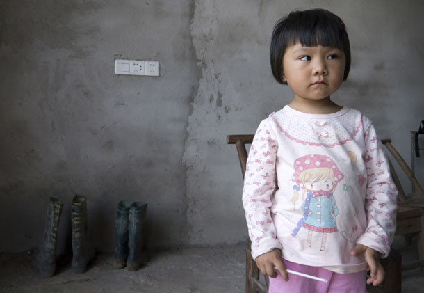 Two-year-old Xu Yilin, whose blood, according to her family, has been shown to have almost three times the national limit for lead exposure in children, stands in a neighbor's house in Dapu, Hunan province, on June 25, 2014. (Photo: Reuters)