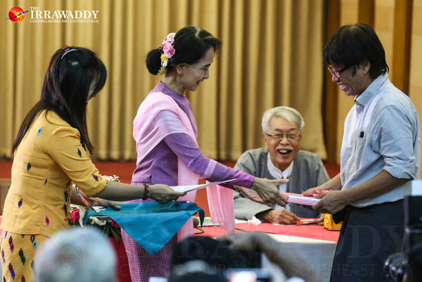 Aung San Suu Kyi, left, gives a certificate to a publisher who donated books to her late mother's Daw Khin Kyi Foundation, during a meeting with artists at the Royal Rose restaurant in Rangoon on Monday. (Photo: Thaw Hein Htet / The Irrawaddy)