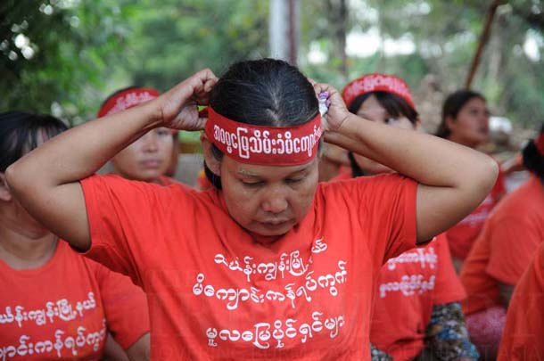A woman ties on a headband identifying her as a former owner of land in Michaungkan village, in Rangoon's Thingangyun Township, which protesters say was confiscated by the Burma Army in the early 1990s. (Photo: Sai Zaw / The Irrawaddy)