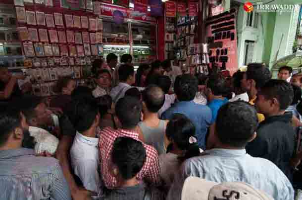A crowd gathers outside a mobile phone shop in Rangoon on Thursday. (Photo: Sai Zaw / The Irrawaddy)