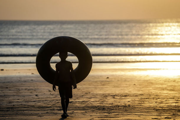 A boy holds an inflatable ring on a beach near Dawei. (Photo: Teza Hlaing / The Irrawaddy)