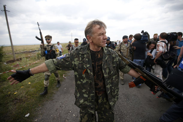 An armed pro-Russian separatist stands guard as a team of Malaysian air crash investigators inspect the crash site of Malaysia Airlines Flight MH17 in Donetsk region on July 22, 2014. (Photo: Reuters / Maxim Zmeyev)