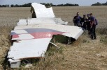 Members of a group of international experts inspect wreckage at the site where the downed Malaysia Airlines flight MH17 crashed, near the village of Hrabove