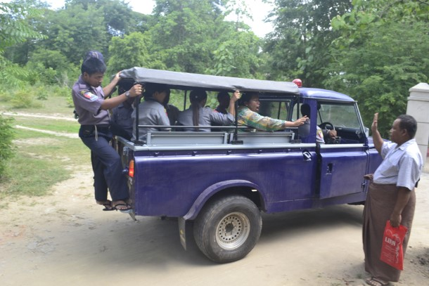 A defendant waves at fellow villagers as she and other farmers are taken away in a police truck after a court hearing at Kantbalu Township Court on July 14. (Photo: Min Naing Thu / The Irrawaddy)