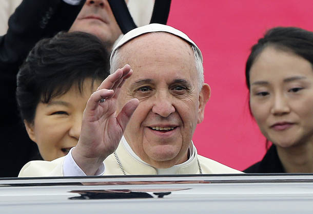 Pope Francis waves upon his arrival at Seoul Air Base as South Korean President Park Geun-hye (partly hidden L) looks on in Seongnam August 14, 2014. (Photo: Reuters)