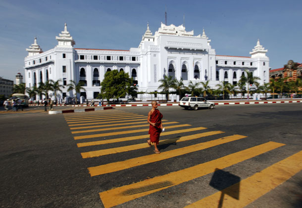 A Buddhist monk crosses the street in front of Rangoon's City Hall in 2011. (Photo: Reuters)
