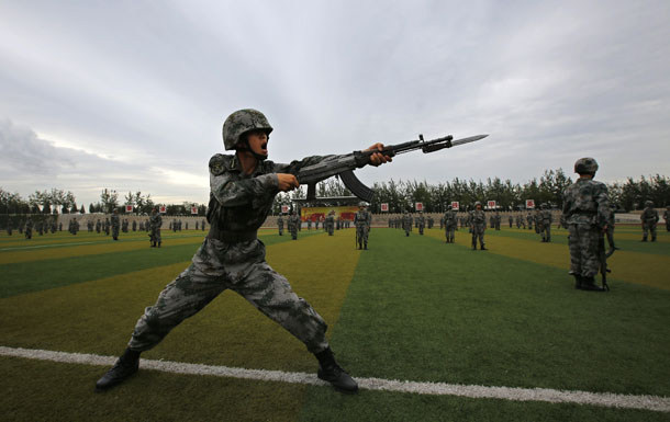 Soldiers of the People's Liberation Army practice with guns in a drill during an organized media tour at a PLA engineering academy in Beijing on July 22, 2014. (Photo: Reuters / Petar Kujundzic)
