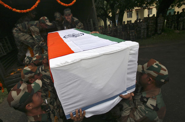 Indian Army soldiers carry a flag-draped coffin containing the body of a colleague killed in a cross-border firing along India's border with Pakistan on July 23, 2014. (Photo: Reuters / Mukesh Gupta)