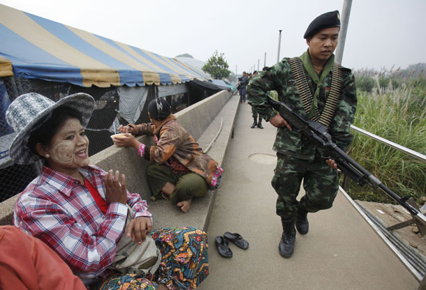 A Thai soldier on patrol walks past migrant workers from Burma sitting at a market in the Thai border town of Mae Sot on Nov. 7, 2010. (Photo: Reuters)