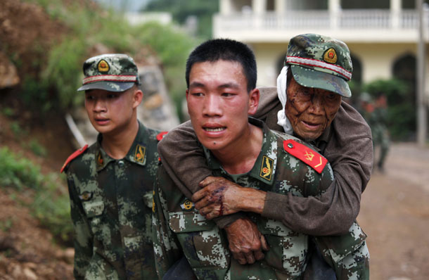 A paramilitary policeman carries an elderly man on his back after an earthquake hit Ludian county of Zhaotong, Yunnan province August 3, 2014. (Photo: Reuters)